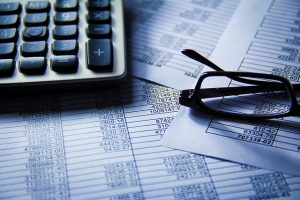 Marketing analytics sheets with glasses and a calculator|PixelMark, El Paso & Las Cruces