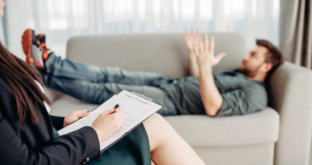 Stressed man lying on a grey counseling couch talking to a therapist