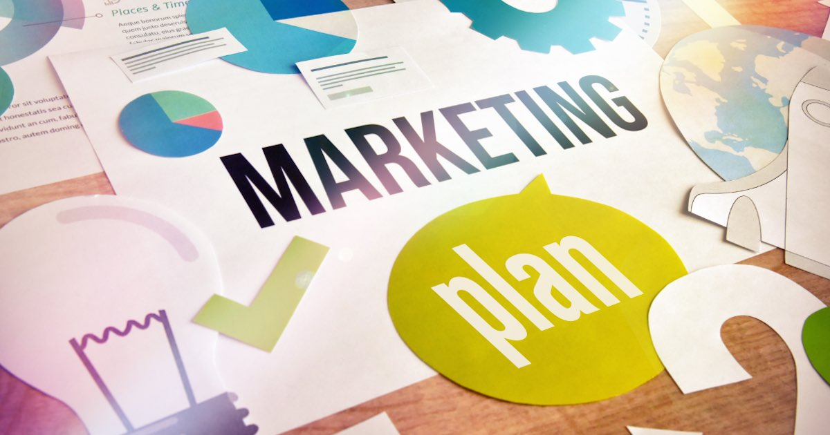 """Marketing plan concept design laid out on a desk with the words """"marketing plan"""" in the center"""